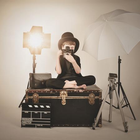 iluminacion: Un niño retro es la celebración de una cámara de la vendimia y el enfoque con diversos equipos de iluminación de la fotografía de un concepto director o película.