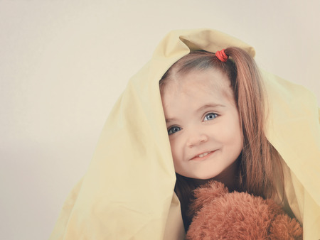 A little child is having fun under a blanket and hiding under the sheet with a teddy bear with copyspace for a message. photo