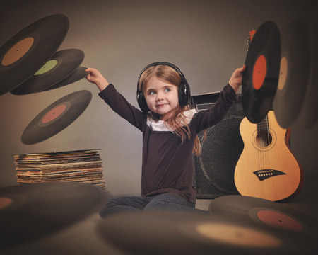 A little child is wearing music headphones with retro vinyl records spinning around on a gray background with an amp and guitar for a party or entertainment concept.