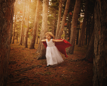 A little girl wearing a white dress and red cape is flying in the wind in the woods with fall leaves for a fairytale or adventure concept.