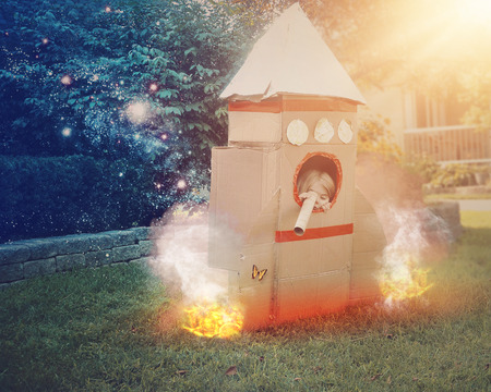 A young astronaut child is sitting in a cardboard space rocket ship pretendning to explore. She is in the front yard imagining she is in space with stars Standard-Bild