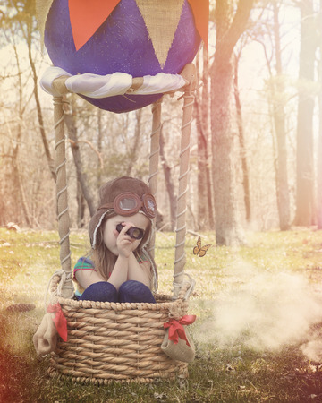 A little child is sitting in a hot hair balloon basket pretending to fly in clouds looking at a butterfly for a creativity or adventure concept.