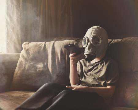 home destruction: A young child is wearing a gas mask with a remote control watching televison on a couch with smoke and poulltion for a clean air concept. Stock Photo
