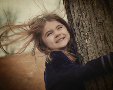 A little child is holding a tree with strong wind blowing in her hair. She is smiling and happy. Use for a weather or freedom concept.