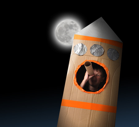 imagine a science: A young boy is in a cardboard space rocket ship pretending to be an astronaut and looking at the moon in the night sky.