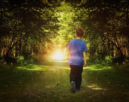 아이는 자유 또는 행복 개념에 대한 경로에 밝은 빛으로 어두운 숲에서 걷고있다. 스톡 콘텐츠