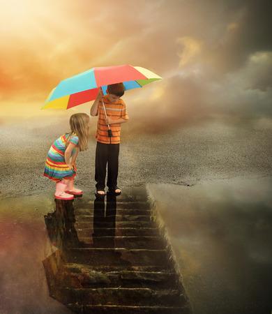 두 아이는 반사에 계단 물 비가 웅덩이에서 내려다보고있다. 소년은 날씨 또는 상상력 개념 무지개 우산을 잡고있다.