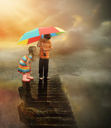 Two kids are looking down at a rain puddle of water with stairs in the reflection. The boy is holding a rainbow umbrella for a weather or imagination concept. Stockfoto