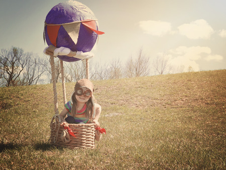 journeys: A little girl is sitting in a hot air balloon pretending to be a pilot flying on a grass field for an imagination or travel concept.