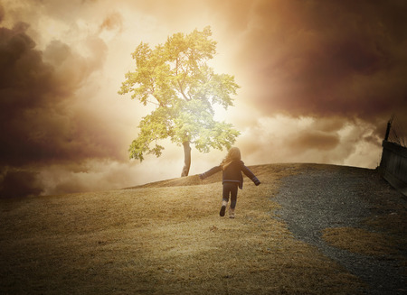 escape: A little child is running up a hill to a glowing tree of light with dark clouds in the background. Use it for a hope, freedom or happiness concept. Stock Photo
