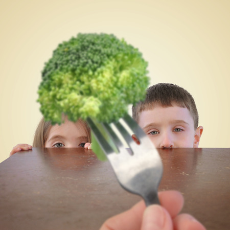 Two little kids are hiding behind a table from a fork with a healthy piece of broccoli on it for a childhood nutrition or picky eater concept. Stockfoto