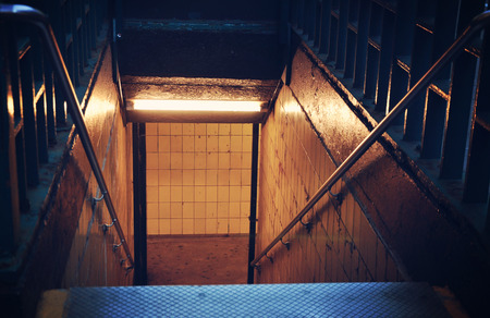 fear: Scary city stairs are leading down to a subway station for a danger or fear concept. Stock Photo
