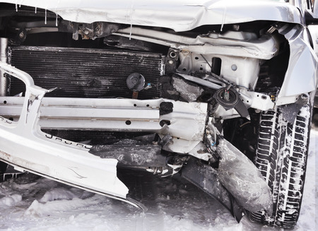 Een close-up van een auto-ongeluk met sneeuw op de banden en kapotte bumper. Gebruik het voor de veiligheid of verzekering concept. Stockfoto