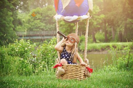 kinderen: Een meisje Sittin in een hete luchtballon mand in het park te doen alsof om te reizen en vliegen met een pilot hoed op voor een creativiteit of verbeelding concept. Stockfoto