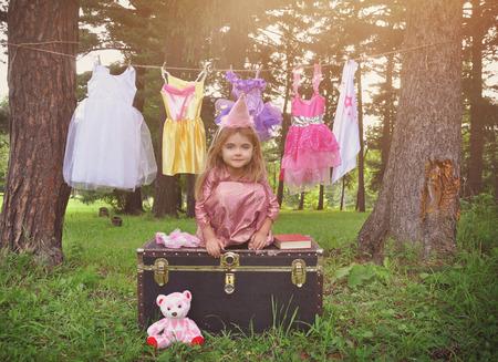 mignonne petite fille: Un petit enfant est petending être une princesse à l'extérieur avec des vêtements suspendus relookings sur une corde à linge pour un concept de l'imagination ou la créativité. Banque d'images