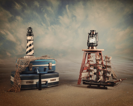 A vintage beach sea background with a little ship, lighthouse and suitcases for a travel or destination idea. Add your text to the copyspace.