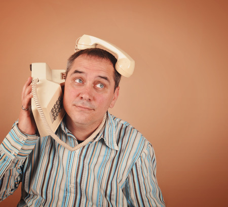 telephone: A retro 1970s man is using an old telephone in an unusual funny way on an isolated background for a communication or technology concept.