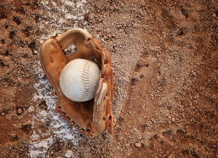 infield: A closeup of an old baseball and glove on a dirt background with copyspace for a message for a sport or recreation concept.