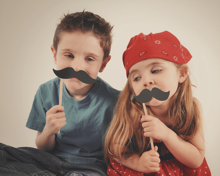 Two children are playing dressup with fake mustaches on an isolated background for a creative or imagination concept.