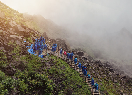 Tourists are walking up a stairway to Niagara Falls with wet water mist and blue raincoats on for a travle or nature concept.