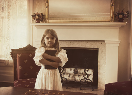 A young vintage child is holding a reading book inside an old fashioned home for an education or generation concept.
