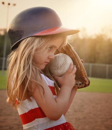 작은 아이는 스포츠 또는 레크리에이션 개념 동안 미트 장갑 흙 필드에 야구 게임을하고있다.