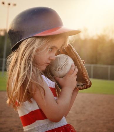 mitt: A little child is playing a game of baseball on the dirt field with a glove mitt on for a sport or recreation concept.