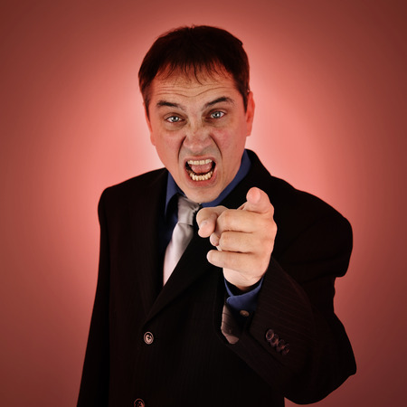 tardy: A mean angry boss is pointing his finger on an isolated background for a business failure concept.