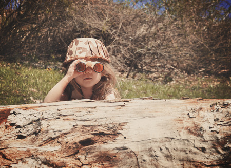 A little girl is hiding behind an old log in the woods with a camouflage hat and binoculars searching and playing for an imagination or exploration concept. Stock Photo