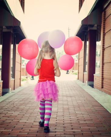 어린 소녀는 행복과 자유 개념에 대한 외부 벽돌 길을 산책하는 다채로운 풍선을 들고있다.