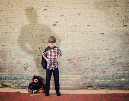 A superhero boy is standing by an empty vintage brick wall with a cap and large shadow to represent strength, imagination or dream concept.