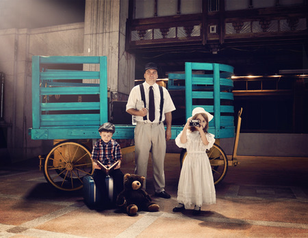 An old fashioned vintage family is waiting in an old train station by a luggage cart for a vacation or travel concept.