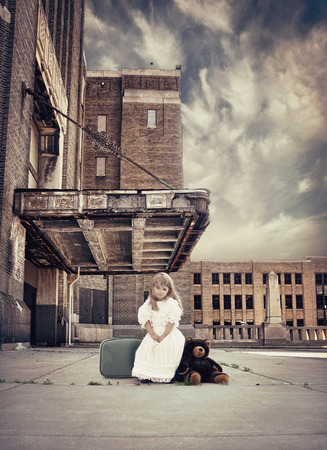 child protection: A little child is sitting on a travel suitcase by an old building with teddy bear next to her for a strength or protection metaphore. Stock Photo