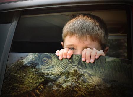 dinosaurio: Un niño asustado joven está mirando por la ventanilla del coche a un peligroso dinosaurio T-Rex para una imaginación, la historia o el concepto de viaje.