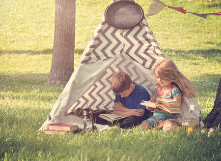 Two Children are sitting in a tent tipi reading books and learning outside in the spring for an education or activity concept for kids. Stock Photo