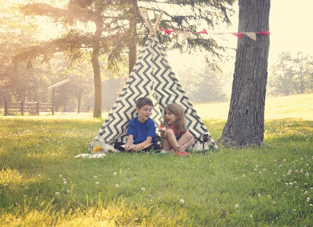 Two children are sitting in a tent tipi and holding a butterfly with a nature summertime background for an imagination or happiness concept.