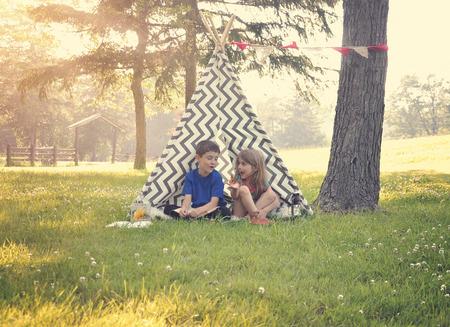 niñas jugando: Dos niños están sentados en un tipi tienda de campaña y la celebración de una mariposa con un fondo de naturaleza de verano para un concepto de la imaginación o la felicidad.