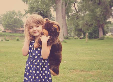 mädchen: Ein junges Mädchen mit einem Stofftier Teddybär spielt auf dem Rücken außerhalb für eine Freundschaft oder Liebe Konzept.