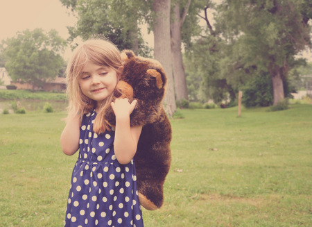 jolie petite fille: Une jeune fille joue avec un animal ours en peluche sur son dos à l'extérieur pour un concept de l'amitié ou de l'amour. Banque d'images