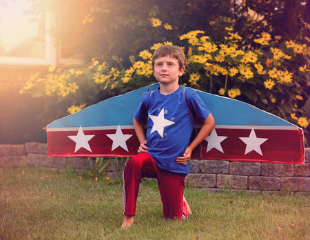 imagine a science: A young boy is pretending to be a pilot with wings and stars in his fromt yard for an imagination or dream concept.