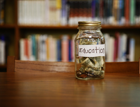 college fund savings: A money glass jar filled with dollars and coins with an education label is on a desk in a library with copyspace for a savings or tuition concept. Stock Photo