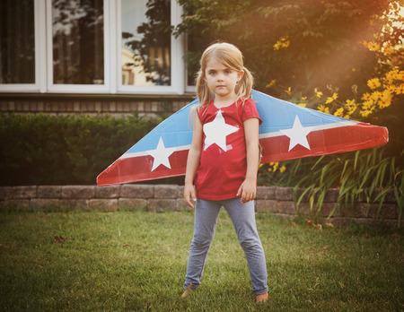 작은 아이는 그들에 별 공예, 상상력 또는 탐사 개념 파일럿 척으로 만든 종이 비행 날개를 입고있다.
