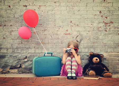 A photo of a vintage child taking a picture with an old camera against a brick wall with balloons and a teddy bear for a creativity or vision concept. Stockfoto