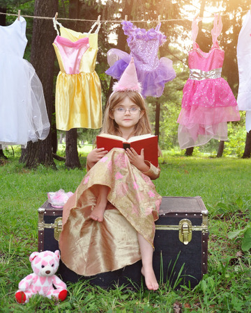 story: A little girl is sitting outside wearing a princess costume reading a story book with glasses on for an education or imagination concept. Stock Photo