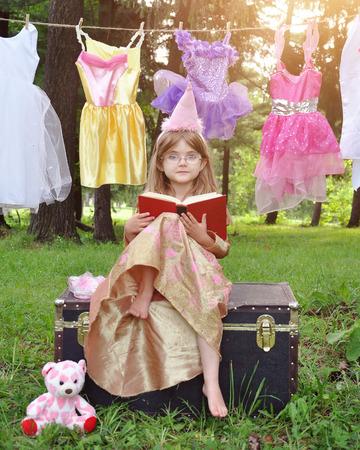 suspenso: Una ni�a est� sentado fuera llevaba un traje de princesa de la lectura de un libro de cuentos con gafas en un concepto de la educaci�n o de la imaginaci�n. Foto de archivo
