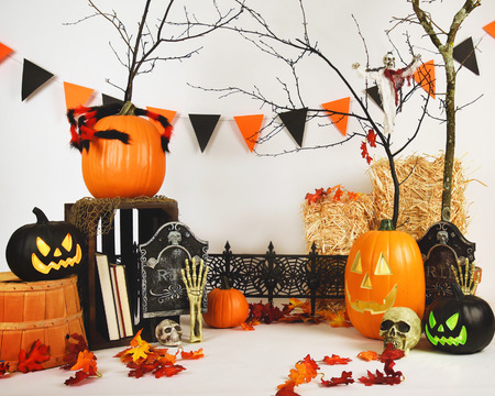 A studio halloween setup with various scary objects in the background on a white backdrop. There are pumpkins and skulls in the scene.