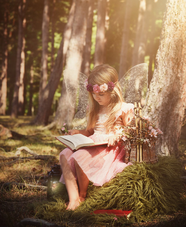 A little girl is wearing white sparkle fairy wings outside in the woods reading a fairytake book for an education or magical story concept