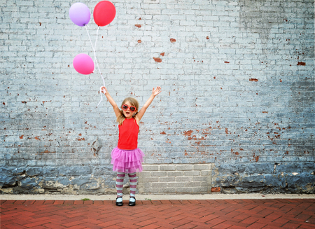 A little child is holding colorful balloons against a textured brick wall and waering sunglasses for a happiness or celebration conecpt. Stockfoto