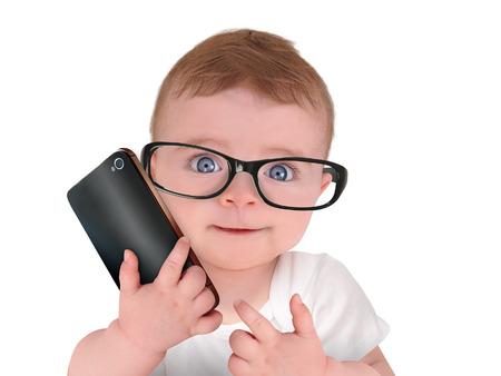 cell: Ein nettes kleines Baby trägt Brille und reden über ein Mobiltelefon auf einem isolierten weißen Hintergrund für ein Humor oder Kommunikationskonzept.