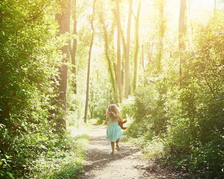 작은 아이는 행복과 자유 개념 나무에 햇빛과 자연 산책로를 실행 중입니다.